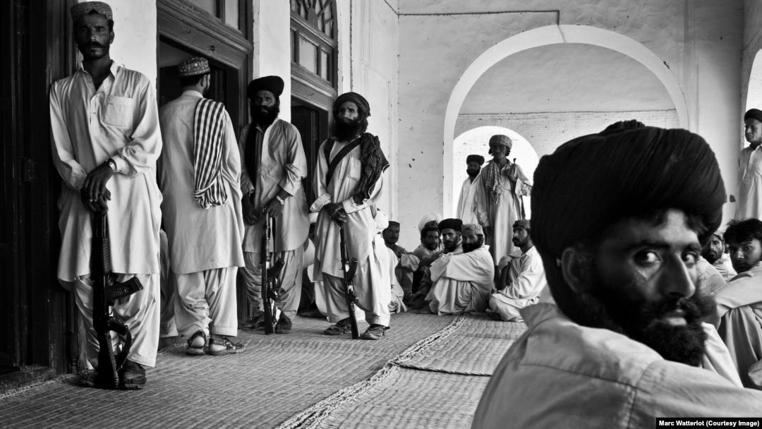 Outside the front door of the late tribal leader Nawab Akbar Khan Bugti's home, several Bugti tribesmen stand guard, while others wait for an audience with their chieftain (file photo).